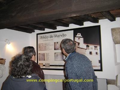 Leitura atenta do painel informativo sobre as antigas prisões